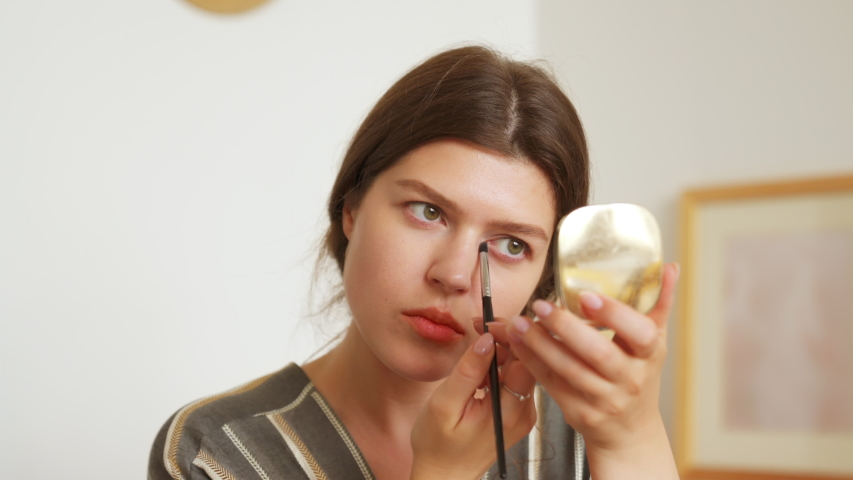 Young woman looks in the mirror, holds a brush and applies shadows on the eyelids. Prepare getting ready in the morning, smiling beautiful girl doing make up put cosmetics on face. | Shutterstock HD Video #1056187970