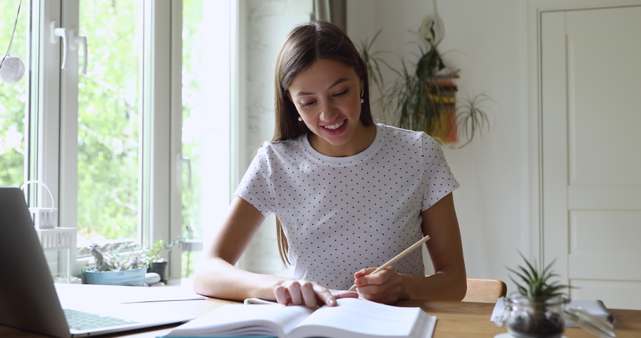 Student girl sitting at desk holds pencil writing essay read textbook, do homework enjoy easy interesting learning process, self-education activity, higher education, gain knowledge, brainwork concept Royalty-Free Stock Footage #1056190217