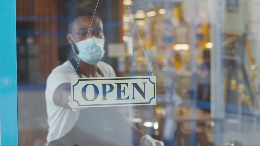 African waiter in mask and gloves putting open sign on cafe door. Afro-American young coffee shop owner reopening place after lockdown because of quarantine Royalty-Free Stock Footage #1056195548