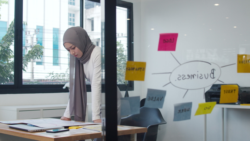 Asia muslim lady drawing work plan think information reminder on paper in new normal office. Working from home, remotely work, self isolation, social distancing, quarantine for coronavirus prevention. Royalty-Free Stock Footage #1056195980