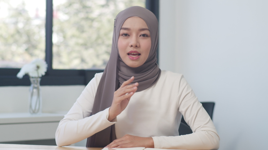 Asia Muslim lady looking at the camera talk to colleagues about the plan in a video call in a new normal office. Working from home, remotely work, quarantine for coronavirus. Royalty-Free Stock Footage #1056199202