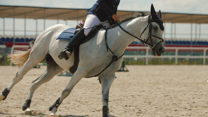Young woman riding brown horse at show jumping competition on sandy parkour arena. Competitive rider galloping at training arena outdoor. Equestrian sport, slow motion.