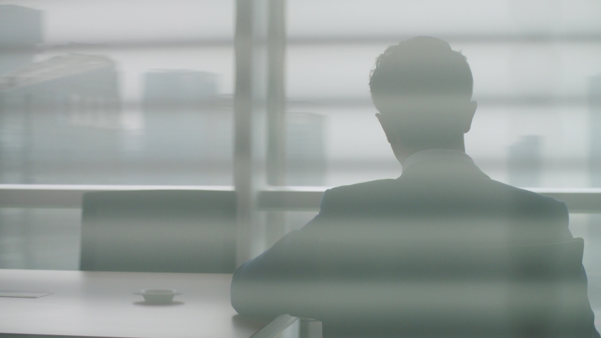 Rear view of mature asian business executive standing up from chair stopping at window looking out at cityscape  | Shutterstock HD Video #1056200057