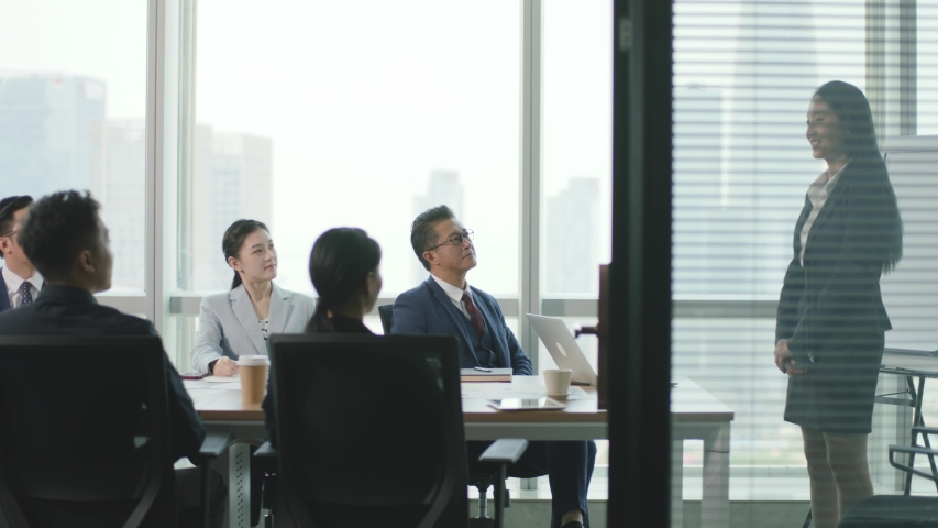 young asian business woman speaking during team meeting in conference room of modern corporation Royalty-Free Stock Footage #1056200060
