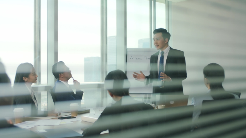 Through the glass and blinds shot of a team of asian business people men and women meeting in modern office conference room | Shutterstock HD Video #1056200063