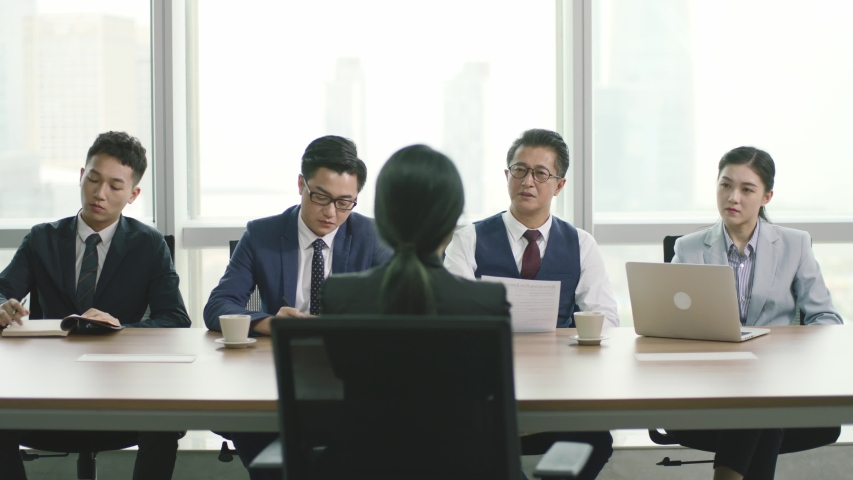 rear view of a young asian business woman being interviewed by a group of human resources executives in conference room of modern corporation Royalty-Free Stock Footage #1056201257