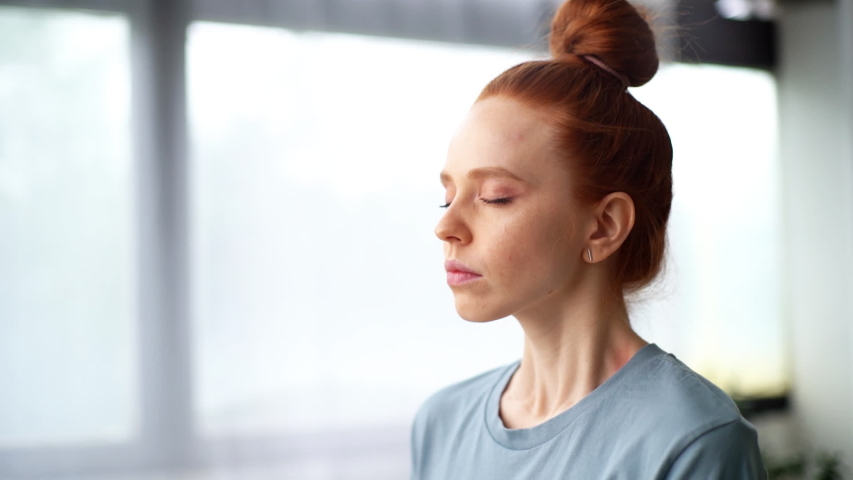 Close-up face of focused redhead young woman doing breathing yogic practices at the home office. closed eyes meditating on background of large window. Cute lady is making deep breath-exhalation. Royalty-Free Stock Footage #1056207413