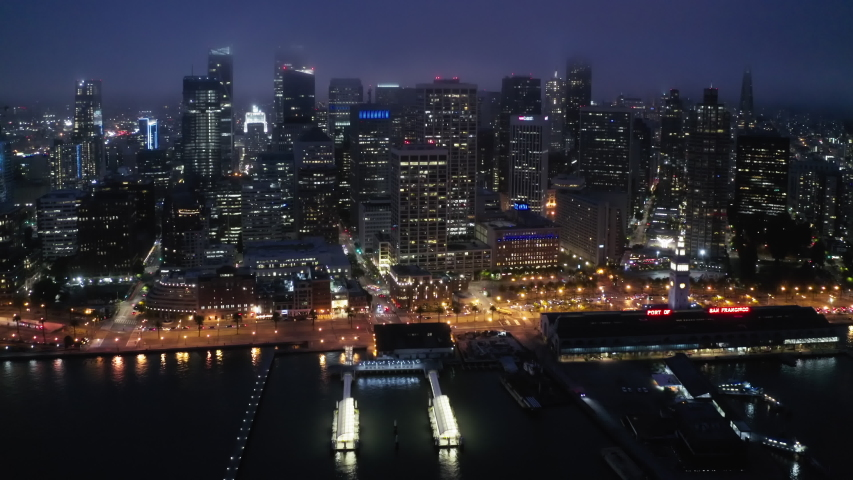 Cinematic aerial panorama of beautiful American city at the bay at night time. Waterfront skyscrapers and streets lights illuminating the night. Beautiful architecture of urban view. 4K San Francisco