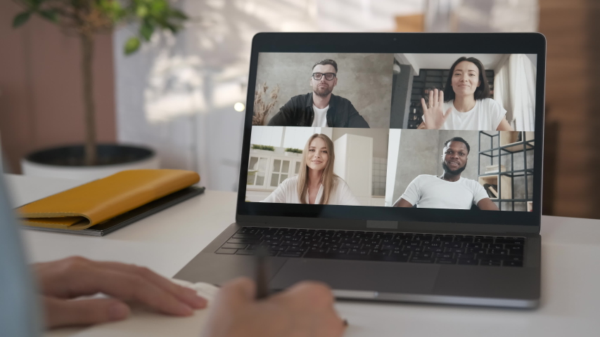 Discussing project online. Over shoulder close up view. Group video call. Remote communication of happy multiracial young people. Working from modern home office. Business chat conference. Closeup 4K