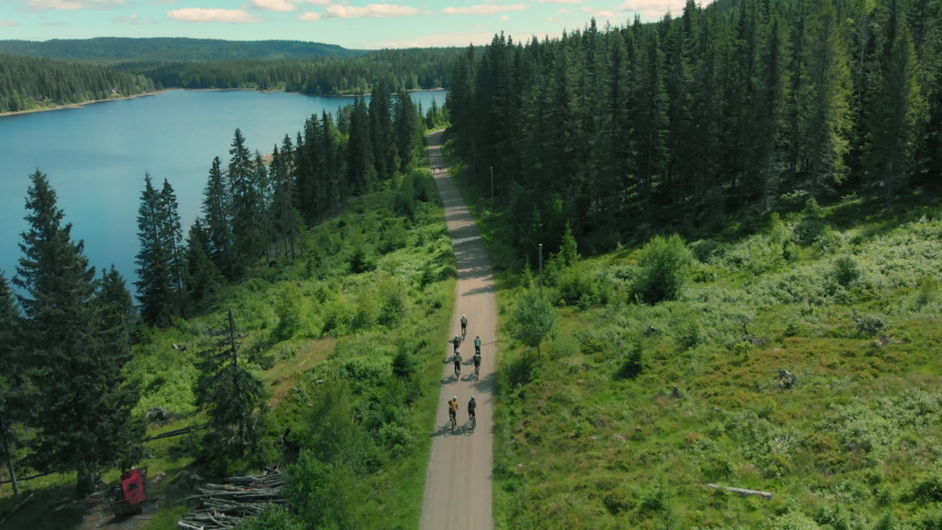 Group of cyclists team ride down gravel mountain road in national park or forest. Friends on bikes ride together have fun outdoors. Aerial drone shot of cyclists ride beautiful epic setting landscape | Shutterstock HD Video #1056221954