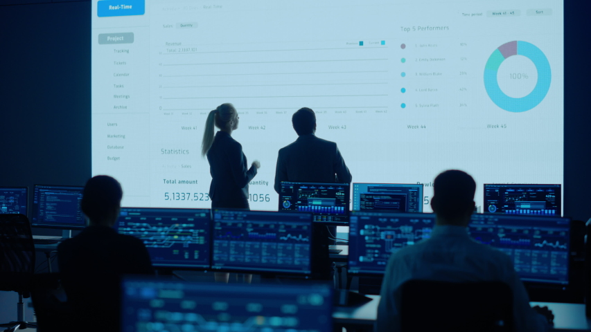 Project Leader and Chief Executive Discuss Data Shown on Big Display. Screens Show Infographics, Charts, Finance Analysis, Stock Market, Growth. Telecommunications System Control Room Royalty-Free Stock Footage #1056222701