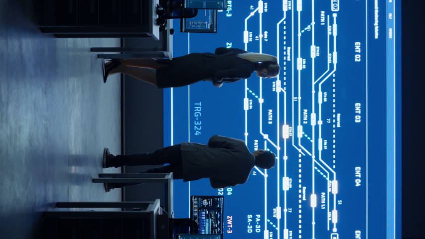 Project Manager and Computer Science Engineer Talking while Using Big Screen Display Showing Infrastructure Infographics and Data.Telecommunications System Control Room. Vertical Screen 9:16   Shutterstock HD Video #1056222725