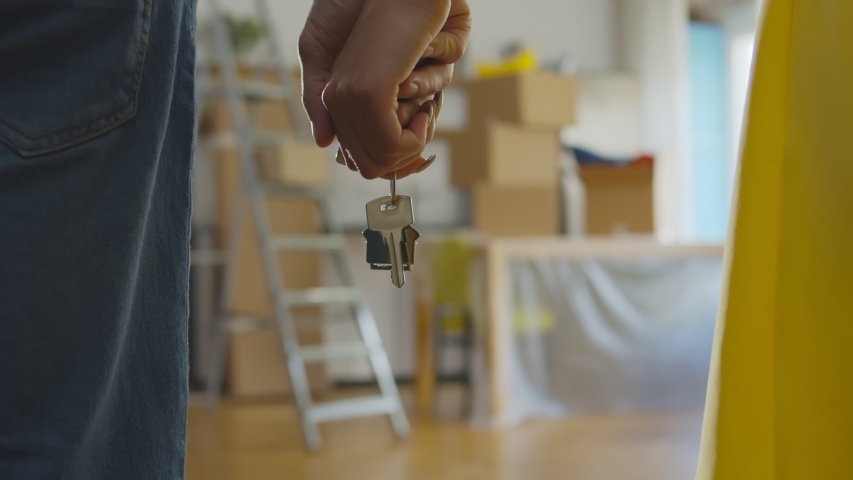 Close up of couple holding hands and keys to new apartment over background with boxes. Happy young family buying or renting new house and moving in together Royalty-Free Stock Footage #1056222965