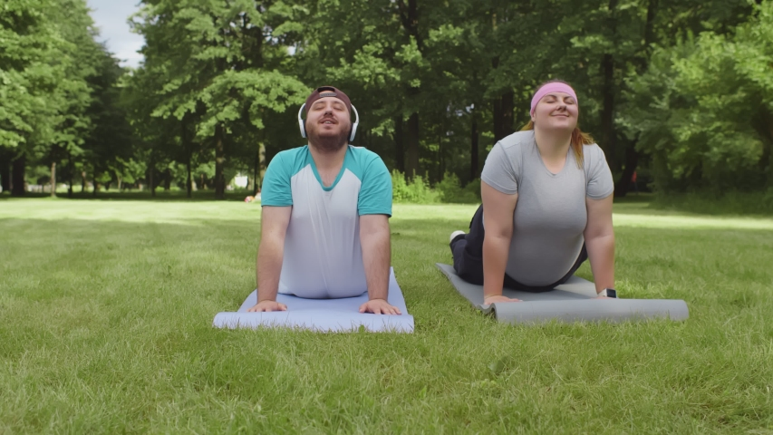 Overweight couple training together in park on sunny day. Fat man and woman doing yoga exercises together on fitness mat outdoors. Weight loss and healthy lifestyle concept
