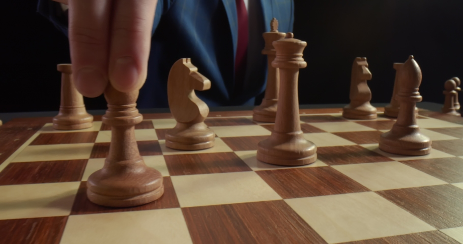 Hand of confident businessman use bishop chess piece white playing chess game. Grandmaster making move isolated on black background. Business strategy for win and success concept   Shutterstock HD Video #1056223025