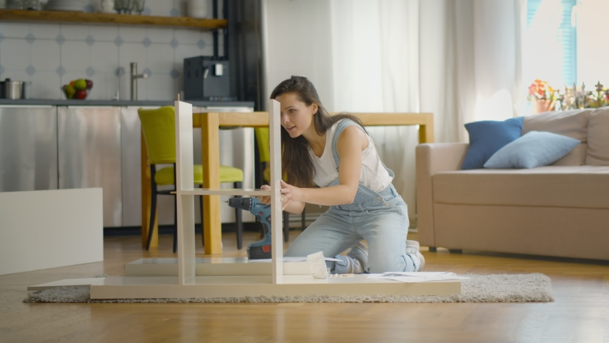 Young woman doing DIY repairs at home putting together self-assembly furniture. Happy young lady successfully folding new bookshelf sitting on floor at home | Shutterstock HD Video #1056223112