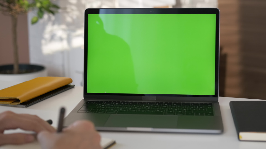 Girl looking at green screen laptop computer in living room watching movie, video content. Business woman or female freelancer working from home office.  Royalty-Free Stock Footage #1056226031