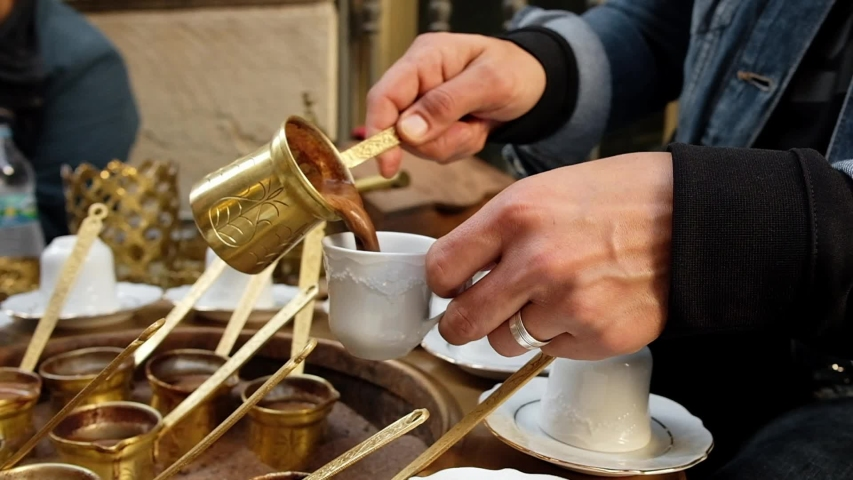 Woman's hands pouring traditional turkish coffee in a cup. Traditional method of making turkish coffee in cezve on hot sand in Turkey