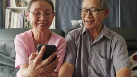 Asian old woman and old man hold mobile phone or tablet for talking and smiling on video call with son, daughter and grandchildren at home. Grandparents feel happy with communicate via internet.