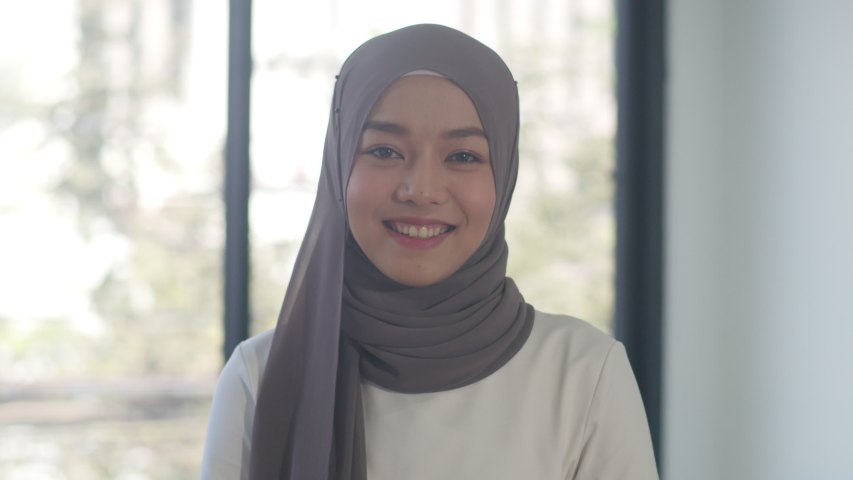 Portrait of successful beautiful executive businesswoman casual wear looking at camera and smile, happy in modern office workplace. Young Asia muslim lady stand relax in contemporary coworking space. Royalty-Free Stock Footage #1056232652