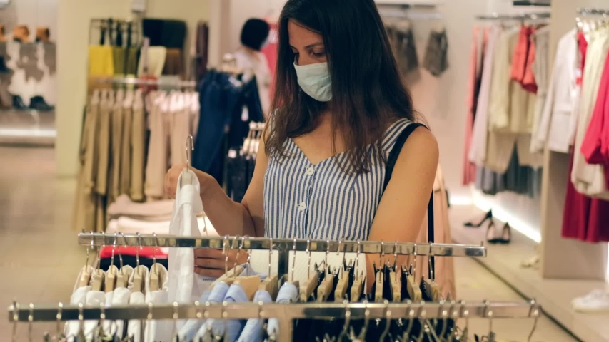 Starting a small business, a pretty girl wearing a protective mask is choosing clothes on the shelves of a store after the quarantine was lifted due to the coronavirus and the pandemic. Woman shopping Royalty-Free Stock Footage #1056235148