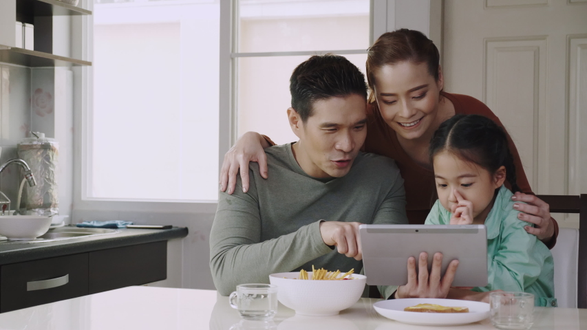 Happy Asian family. Mom and dad are playing a tablet with a cute daughter on the dining table in the home. People are video calling with relative or friend. Using high speed internet technology Royalty-Free Stock Footage #1056236039
