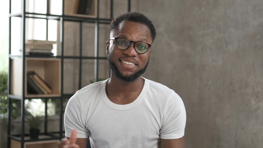 Happy student having online video chat conference looking at camera. Webcam view. Working from home office during the pandemic. Online education training. Portrait african american man in glasses