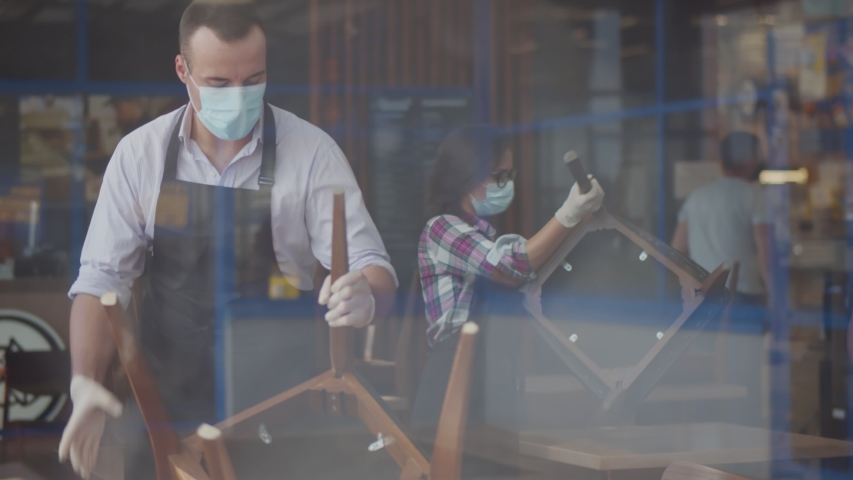 View through window of team waiters in facial mask closing cafe because of quarantine. Restaurant staff cleaning and arranging furniture after closing in evening. Small business and pandemic concept | Shutterstock HD Video #1056238487