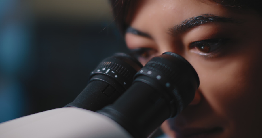 Close up of a female research scientist eyes, looking at samples under microscope.Blue lighting in a dark lab room.Slow motion, slider, shot with BMPCC 4K.Biochemistry, pharmaceutical medicine,science