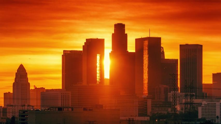 Sunset sun setting behind downtown Los Angeles skyline silhouette. Zoom in on landmark city buildings. Timelapse, 4K UHD.