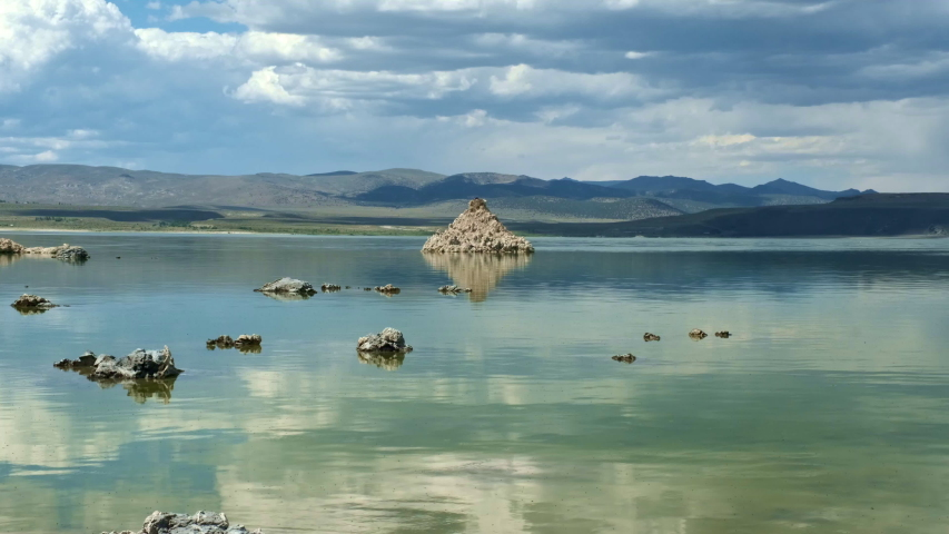 Wide Landscape Shot of Glassy and Smooth Mono Lake California, Featuring Limestone Tufas with Cloud Reflections and Mountains in Background
