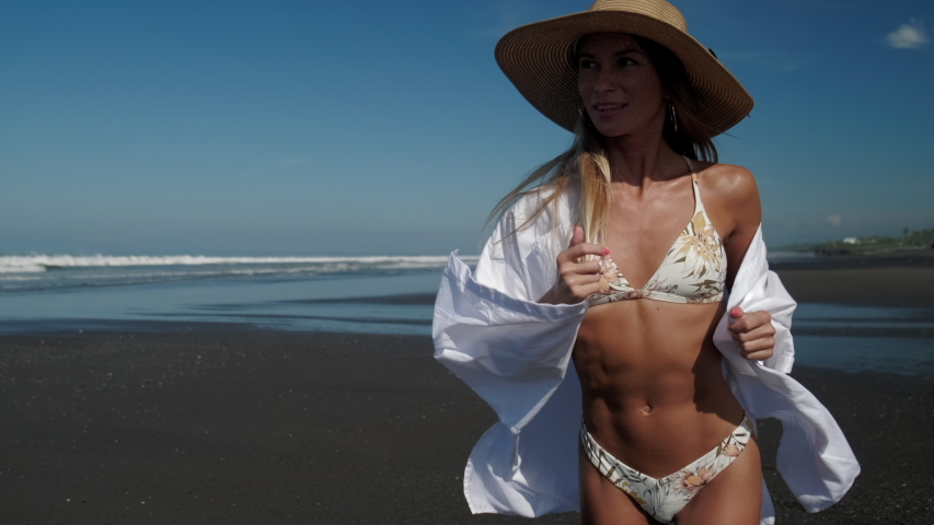 Pretty tanned blonde in bikini, white shirt and straw hat running and posing on the black sand beach. Happy woman enjoying summer heat and vacation freedom