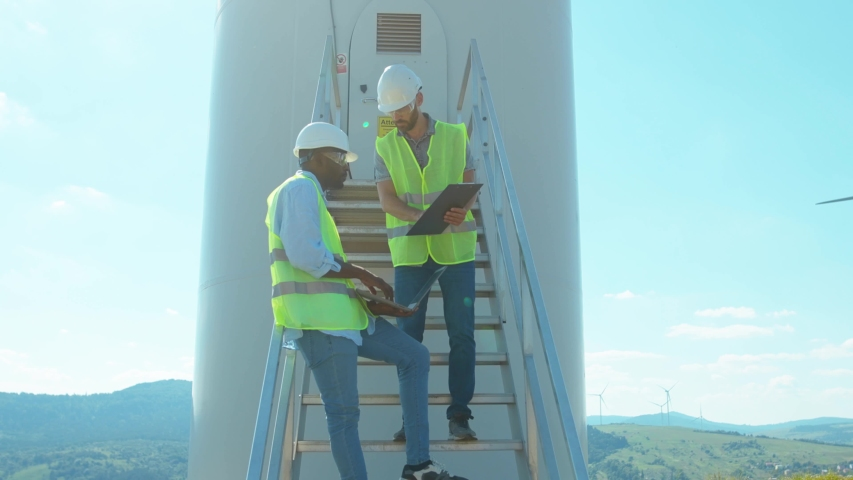 Two engineers men in uniform discuss use laptop stand near wind turbines ecological energy industry power windmill field worker renewable slow motion