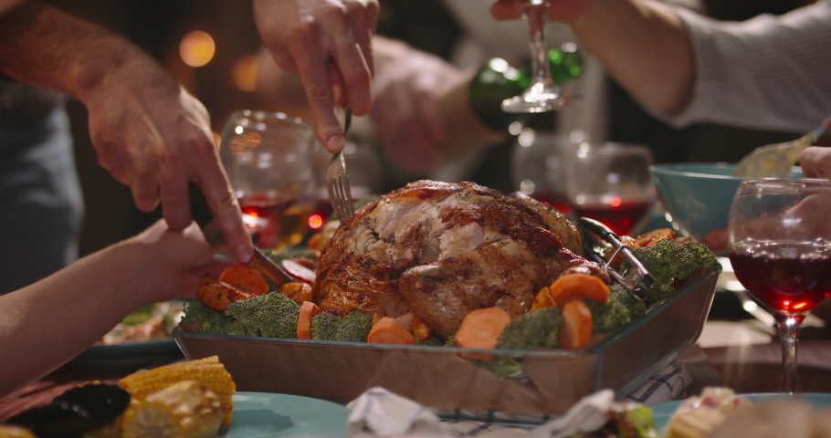 Close up shot of people eating delicious roasted turkey during thanksgiving or christmas dinner party, filling up plates and glasses - food and drink, celebration 4k footage | Shutterstock HD Video #1056257168