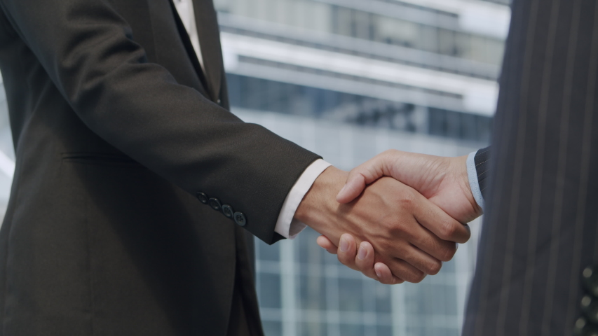 Close up. Hand of two Asian business people gathered to shaking hands agree to a deal or say hello On the background of building in city