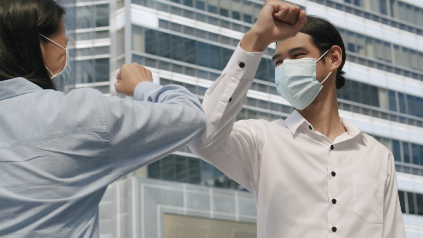 Elbow bumping. Two business people wear mask and greet each other in a new way to prevent the spread of germs and avoid virus covid-19 in the city Royalty-Free Stock Footage #1056261101