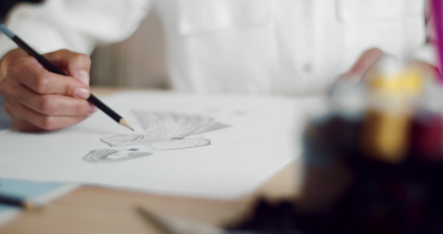 Close up of female designer using pencil and sheet of paper for fashion sketches. Mature woman in white blouse creating design of new clothing collection.