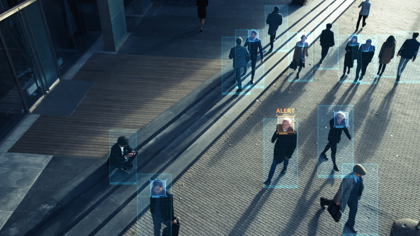 Elevated Security Camera Surveillance Footage of a Crowd of People Walking on Busy Urban City Streets. CCTV AI Facial Recognition Big Data Analysis Interface Scanning, Showing Animated Information Royalty-Free Stock Footage #1056263537