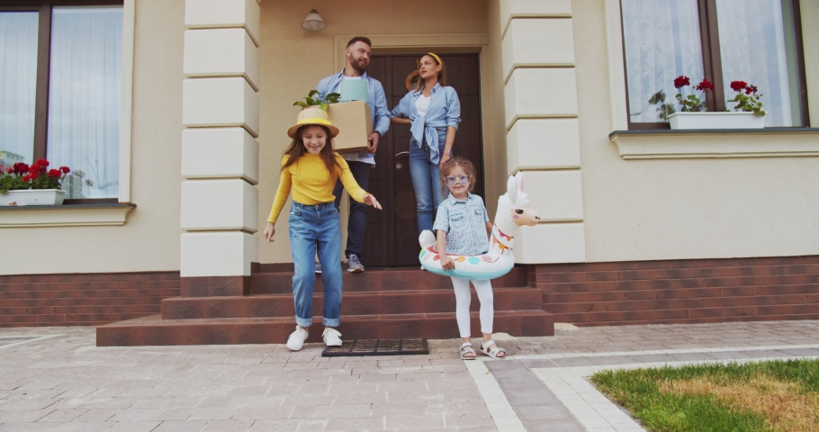 Сouple with amazing children leaving door of newly sold house with things in box and going to car. Family just sold house. Moving to new apartment of young couple. Concept of lifestyle, happy family.