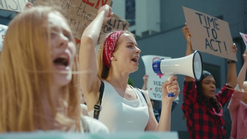 Group of strong powerful women participate in public street demonstration fighting for gender equality. Feminist manifestation. Girl power concept. Resistance. Royalty-Free Stock Footage #1056263930