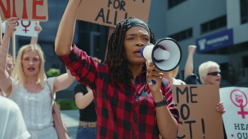 African american woman using megaphone chanting slogans with activists. Female feminist protestors fight for equal men and women rights. Stop sexism.