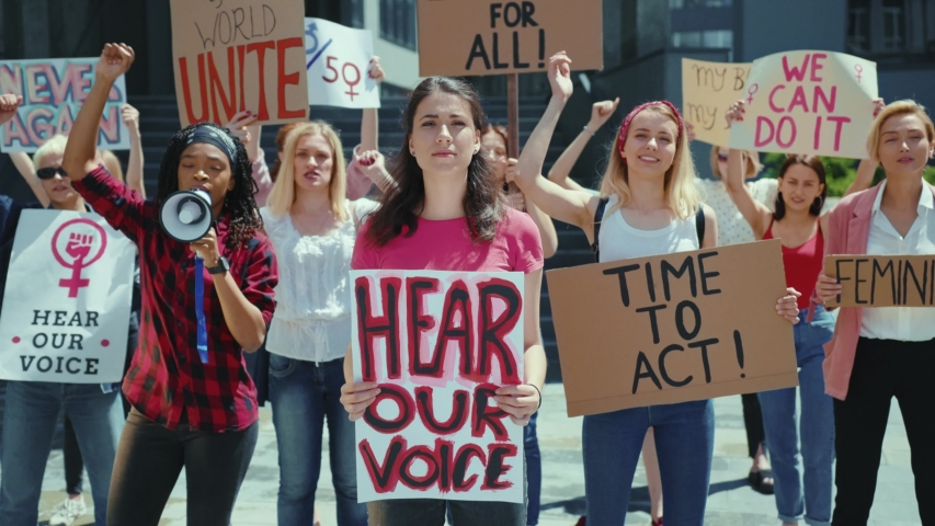 Strong and independent women protesting on street for feminism. Portrait good looking female activist leader with banner stands in front of crowd. Girl power. Protest. Royalty-Free Stock Footage #1056263975