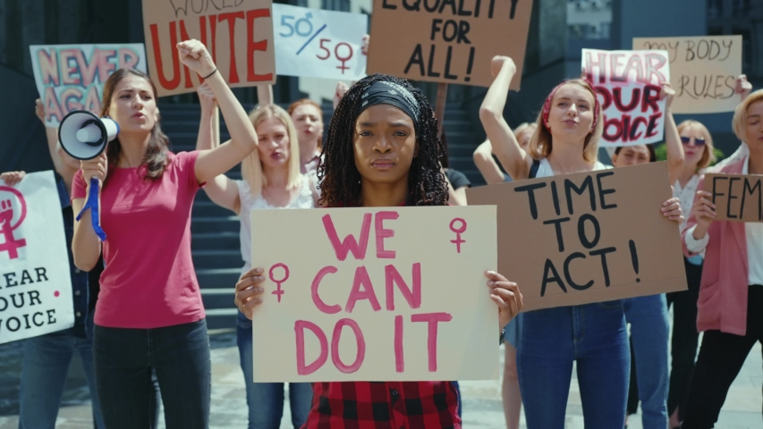 Afro-american woman showing We Can Do It poster on female protest. Crowd of resolute and strong women protesting for gender equality. Feminism promotion.