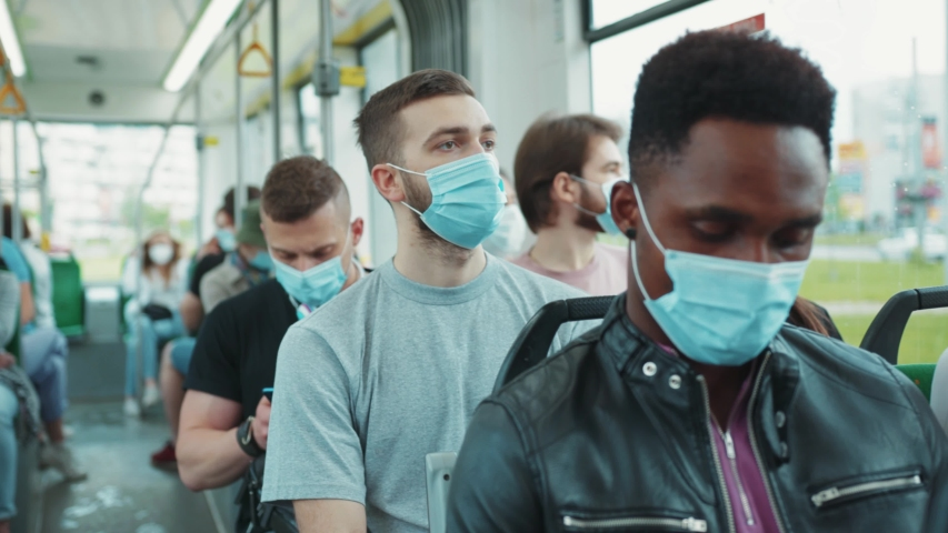 Multi-ethnic passengers in tram wearing protective face masks. Diverse people travel on public transport going to work during quarantine. Health care. Pandemic. | Shutterstock HD Video #1056263993