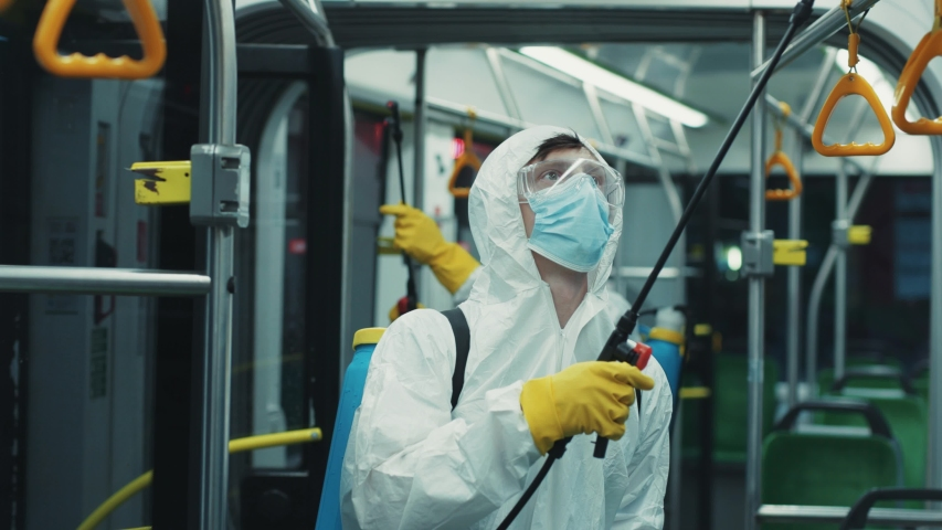 Sanitation worker in white protective suit cleaning the tram with disinfectant spray. Public transport disinfection. Prevention action. Coronavirus. Royalty-Free Stock Footage #1056264065