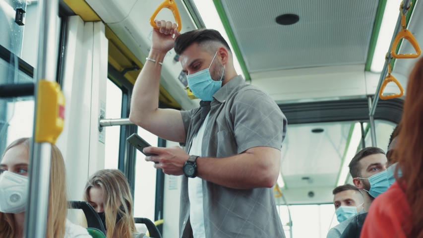Millennial guy in face mask using smartphone in the bus. All passengers having protective masks for safety. Health care measures. Covid-19 infection. Quarantine. Royalty-Free Stock Footage #1056264101