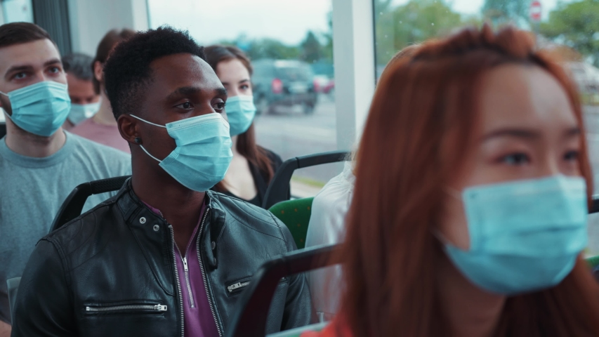 Multi-ethnic men and women driving in public transport on pandemic. Happy passengers removing face masks on end of quarantine. No coronavirus. No more isolation. Royalty-Free Stock Footage #1056264104