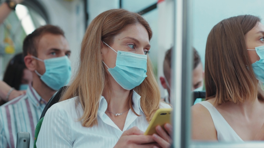 Citizens in face masks using public transport during pandemic. Couple of caucasian women using smartphones drive in the tram.