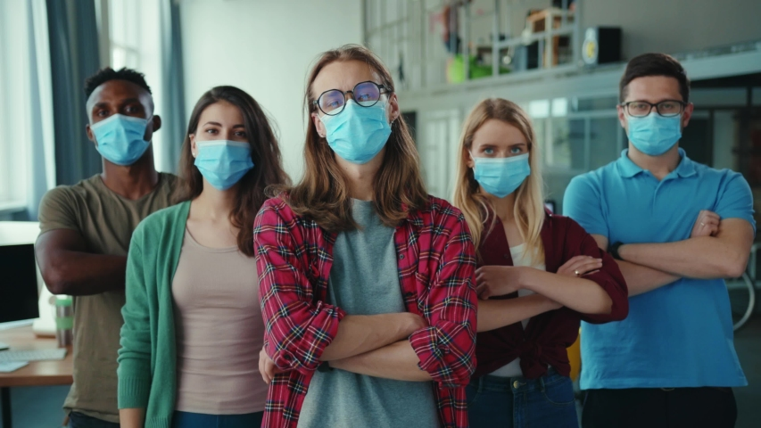 Multi-ethnic team of young ambitious employees wearing face masks, posing with crossing arms in the office. Coworking space. Business people. Corporate. Quarantine. Royalty-Free Stock Footage #1056264134