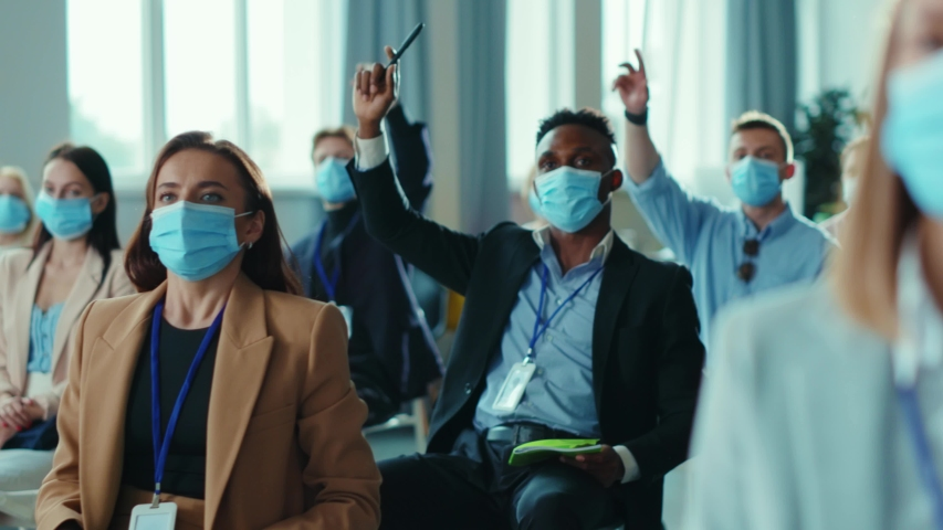 Group of mixed professional employees on corporate meeting raising their hands for voting. Business seminar. Business people. Respiratory masks. Health care. Social distancing. Royalty-Free Stock Footage #1056264164